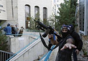An Israeli police officer gestures as he holds a weapon near scene of an attack at a Jerusalem synagogue